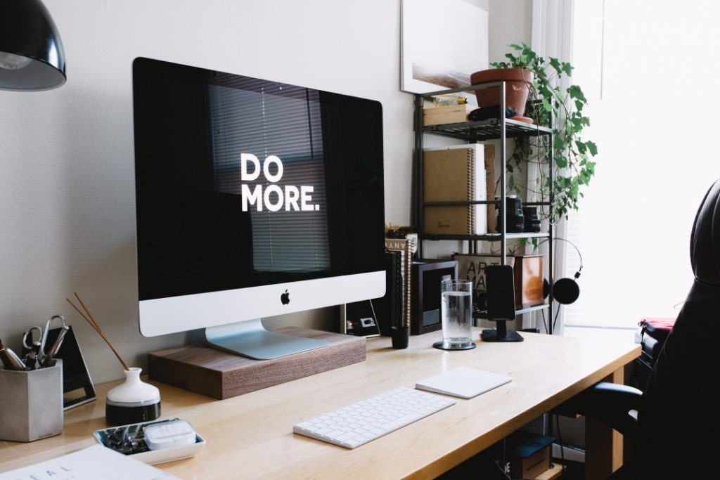 """Computer on desk displaying """"do more"""" as the screen saver. Digital Transformation blog post"""