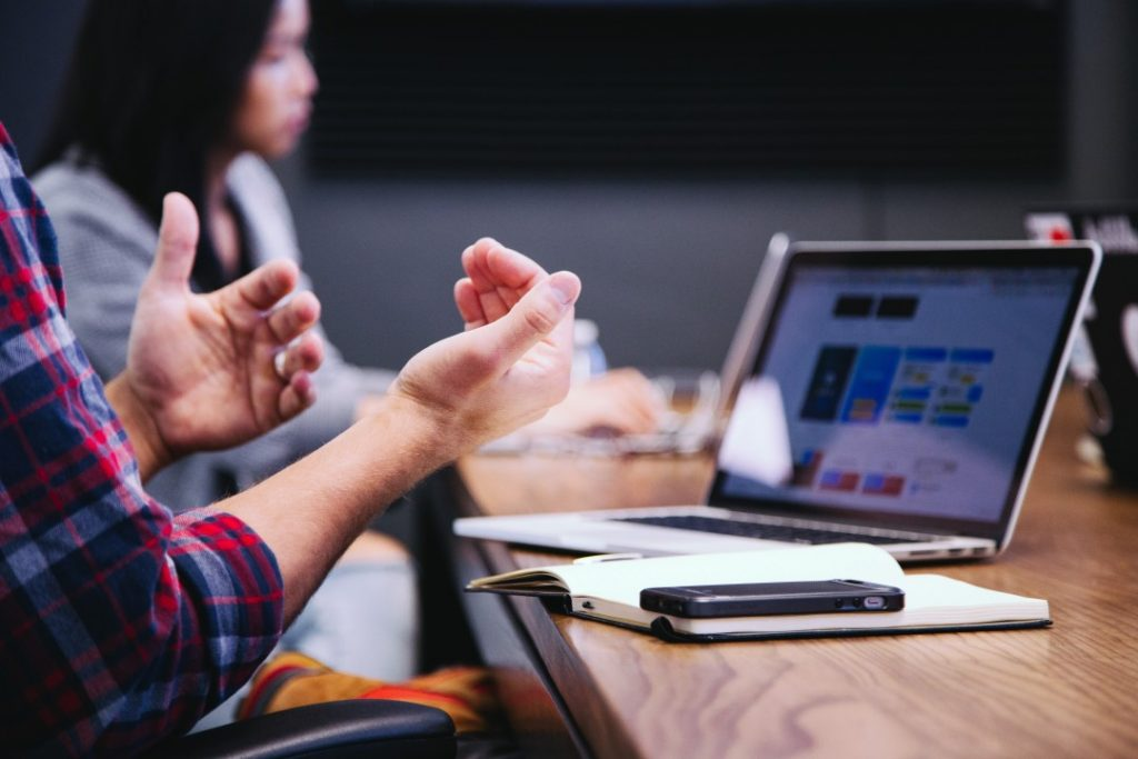 A matting with people talking. Laptops on tables. Can a client-side project manager really improve your rates of project success?
