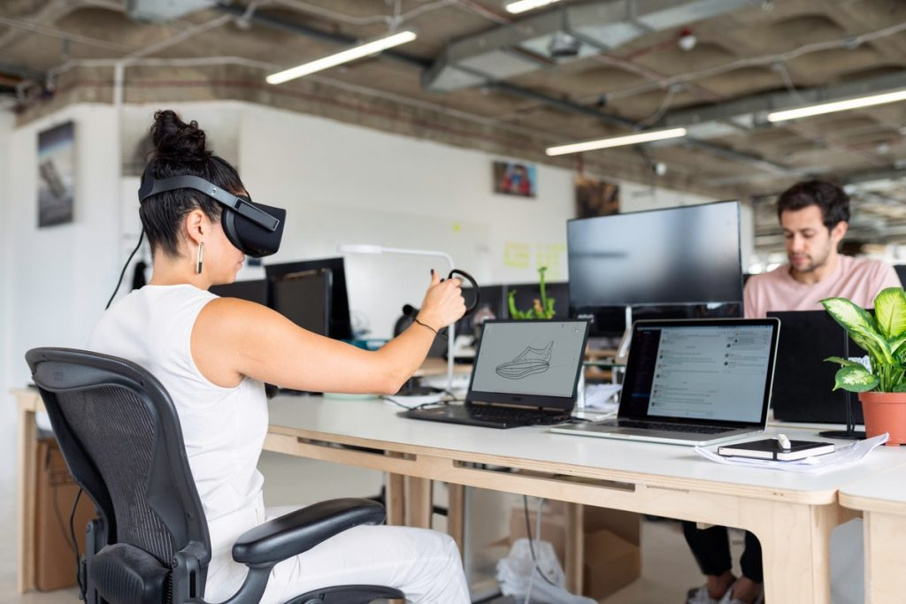 A woman doing virtual reality at a table with laptops on it. - How Technology is Restructuring ever aspect of business