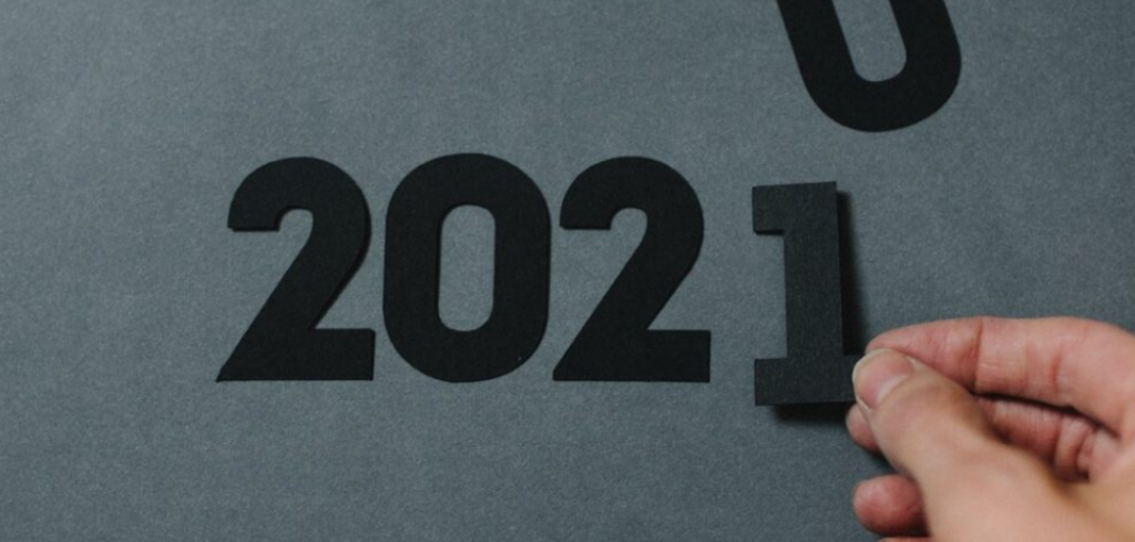 """Someone placing felt numbers onto a grey background to spell out """"2021"""". IT Trends for 2021: How CIOs Can Position for Success"""