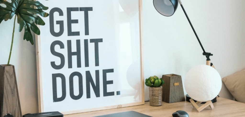 """A white sign learning against a wall with the words """"Get Shit Done"""" in black. There's other decorative objects on the desk. Effective Communication & Collaboration for Remote Teams"""
