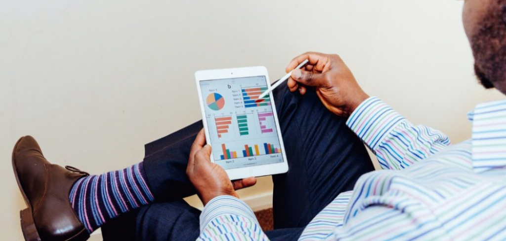 A man sitting in a chair using an ipad displaying charts. Proving Business Case: Tips for Calculating IT ROI